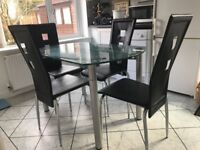 Glass top extending table and four black chairs