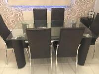 6 seater glass table with 6 brown leather chairs