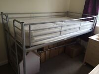 Childs metal frame bed with storage capacity underneath.