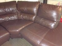 Brown leather corner suite with electric recliner armchair and footstool.