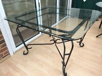 Wrought iron dining or kitchen table. Glass top with bevelled edge