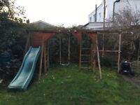 Wooden climbing frame with slide and swing