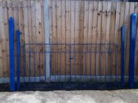 Newly painted blue traditional metal driveway / garden gates with large pointed posts