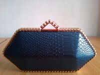 A BLUE CROCODILE SKIN CLUTCH WITH GOLD PLATED EDGES