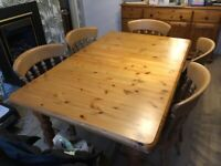 An extendable solid pine dining table and six chairs