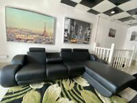 Black leather corner sofa with headrests and cup holders