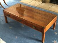 Yew military style coffee table with protective glass topper.