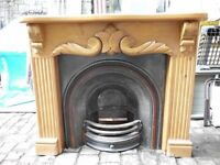 CAST IRON INSET FIREPLACE WITH CALVED WOOD SURROUND