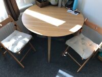 Brown Ikea table with 4 x fold up chairs and cushions.