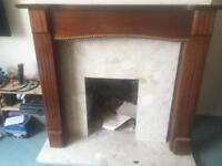 Wooden fireplace surround with marble plinth and wall back