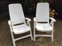 White plastic reclining garden chairs