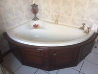 Corner bath with panel.