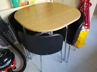 Space saver pine colour table and black chairs