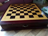 chess set with gold and silver peices in drawers.