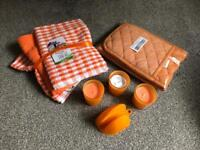Brand new orange kitchen tea towels, oven gloves and candles