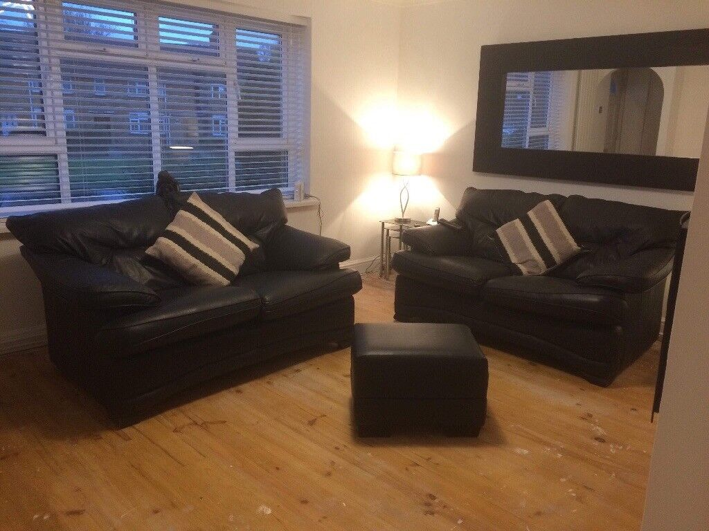 2 leather black sofas and foot stool