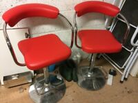 Two Matching Red Hydraulic, Swivel Bar Stools on Chrome Bases.