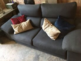 Two-seat grey sofa plus footstool and cushions