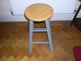 A kitchen stool painted mid grey.
