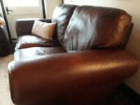 2 two seater leather sofas on wooden square feet.