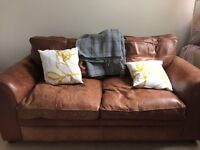 Beautiful brown leather two seater sofa. Fits three people.
