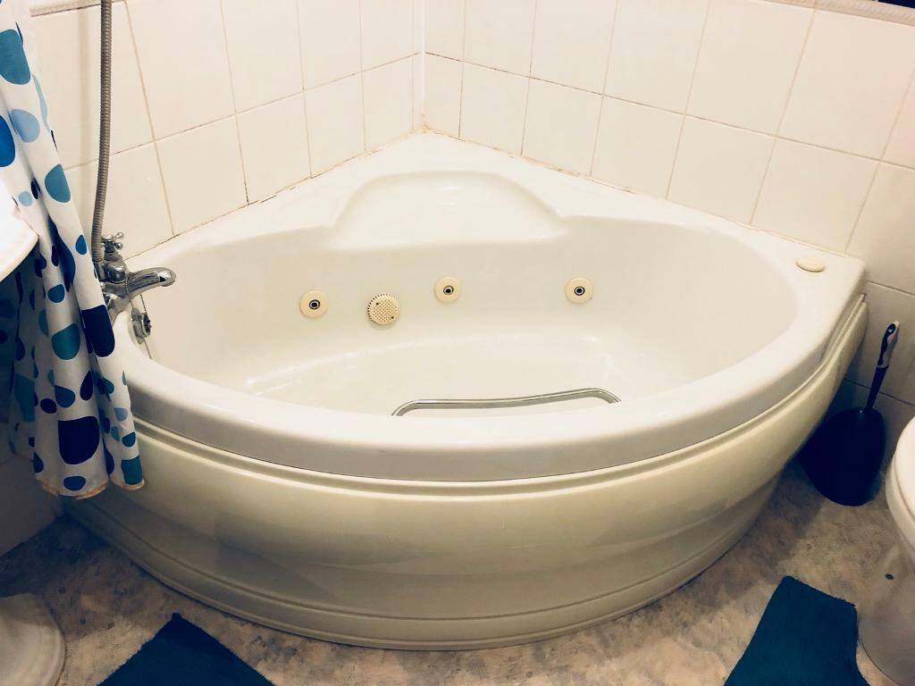 White corner bath (jacuzzi feature but needs attention) and white ...