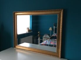 Large mirror, with bevelled glass and carved gold effect frame.