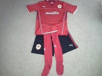 Junior Cardiff City football kit in red, shirt( 30 - 32inch ) shorts ( 30 inch )and socks 4 - 6