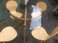 A modern glass round top dining table and 4 chairs can deliver