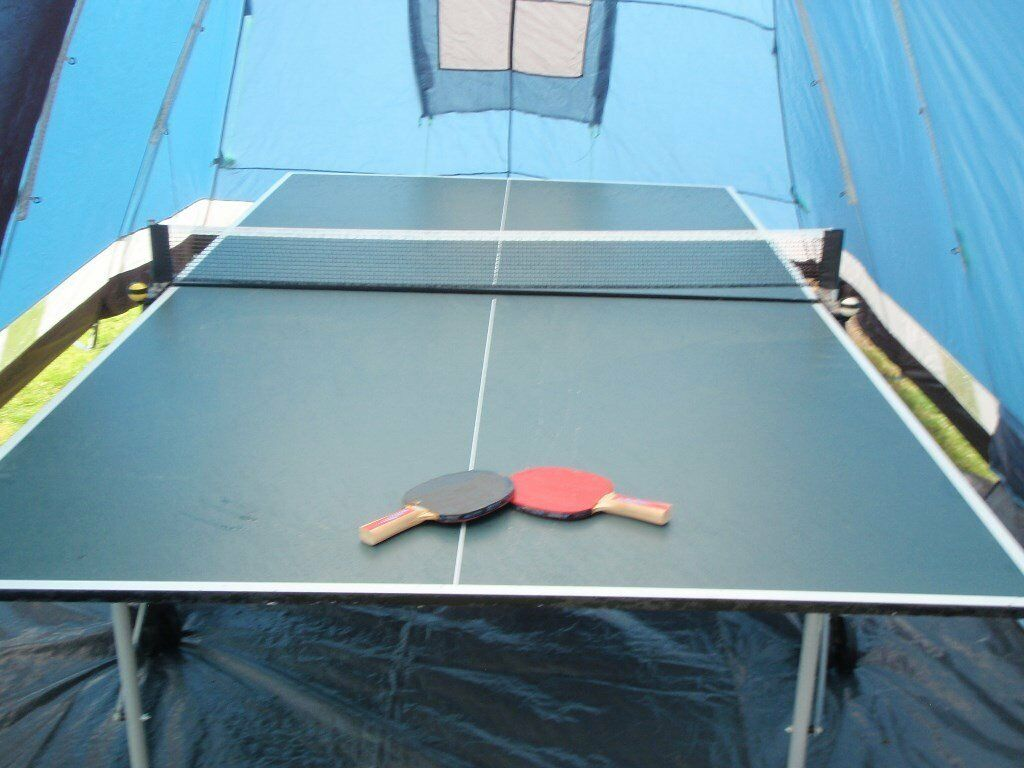 Full size Table Tennis Table on wheels and easily folds up. As new condition. with Bats and Balls.