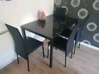Black glass dining table and for chairs