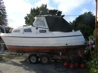 23 ft Cabin boat on braked trailer inboard engine ready to go back in the water at a great price.