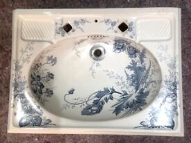 Very old white hand basin with blue pattern