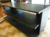 lovely black wood tv stand on castors , four shelves, (118 cms wide) (52 cms height)(40 cms depth)