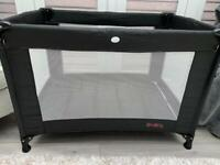 Black travel cot with additional foam matress