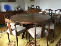 Round teak extending dining table and 10 chairs with matching teak sideboard