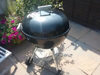 Black Weber kettle charcoal barbecue with Weber chimney.