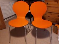 Two orange chairs, used. One has a small couple of chips of paint missing