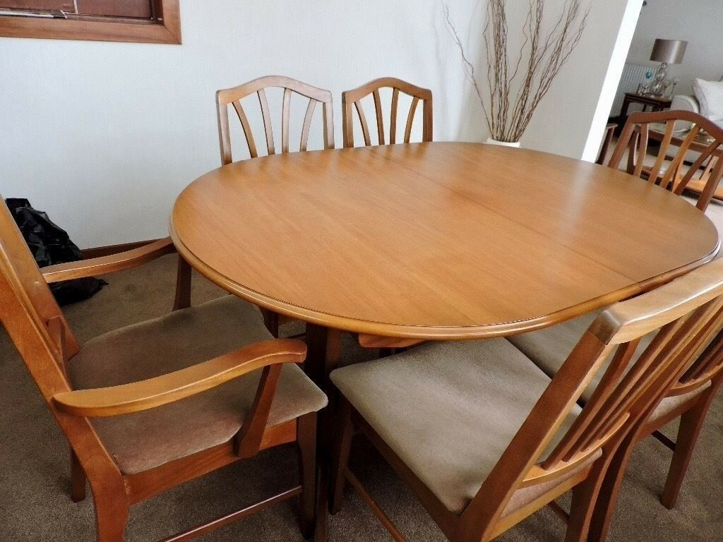 Extending oval wood dining table with six chairs.