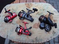 FOUR ASSORTED FISHING REELS.