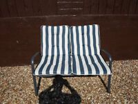 DOUBLE SEAT WITH NAVY AND WHITE CUSHIONS.