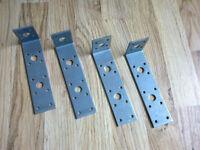 Four large metal brackets