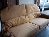 2 Cane Armchairs, 2 seater sofa, footstall all with cushion and coffee table