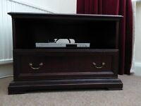 Television unit in mahogany finish with shelf and drawer.