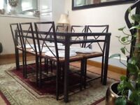 Glass dining table with 6 chairs and white cushions in good condition,