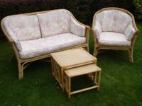 A wicker conservatory set of 2 seater sofa, one chair and nest of 2 small tables with cushions