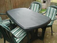 Garden table and four chairs in strong plastic, includes cushions for the seats.