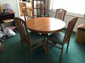 Light Oak extending dining table with five chairs.
