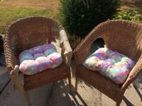 Two wicker chairs and cushion pads