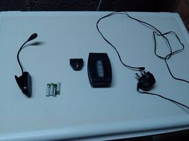 Duracell battery charger and accessories, 4 AAA batteries, and 1 clip on study light